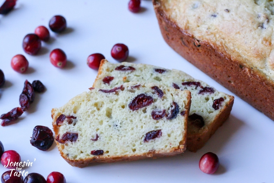 Slices of cranberry eggnog bread surrounded by cranberries