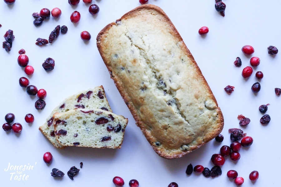 Cranberry eggnog bread surrounded by fresh and dried cranberries