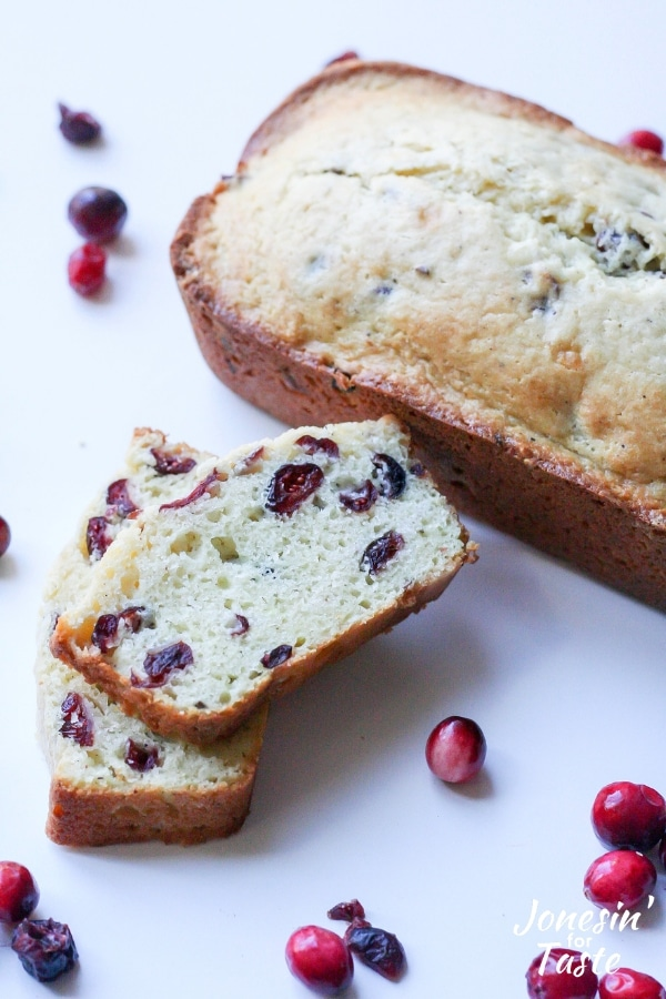 Slices of cranberry eggnog bread next to a full loaf