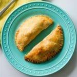 2 baked empanadas sit on a blue plate next to a yellow napkin