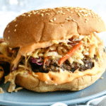 a burger sits on a blue plate. It is spilling over the bun with ingredients like an orange hued sauce and a coleslaw
